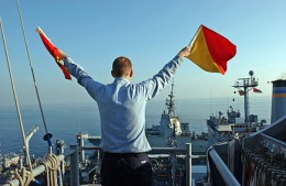 US_Navy_051129-N-0685C-007_Quartermaster_Seaman_Ryan_Ruona_signals_with_semaphore_flags_during_a_replenishment_at_sea.jpg